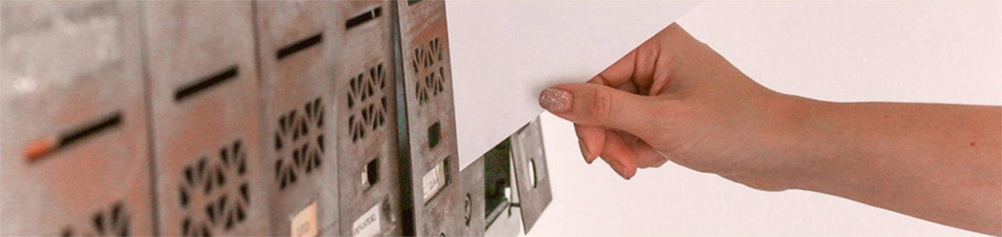 Hand placing envelopes into a post box